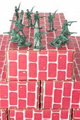 stock photo of top-gun  - Green army men guarding the top of red cardboard brick base - JPG