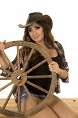 foto of cowgirl  - a cowgirl with a smile on her face holding on to a wagon wheel her tattoo showing - JPG