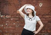 stock photo of blouse  - A smiling young woman in a white blouse and a hat posing against the backdrop of an old vintage brown brick wall - JPG