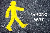 picture of pedestrians  - Yellow pedestrian figure on the road walking towards WRONG WAY - JPG