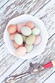 stock photo of chickens  - Colorful farm fresh chicken eggs from free range chickens with an antique egg beater over a rustic wooden background - JPG