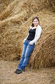 picture of haystack  - Pretty young woman in a white blouse and jeans posing on the background of haystacks - JPG