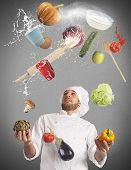 stock photo of juggling  - Playful chef likes to juggle while cooking - JPG
