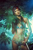 foto of tropical plants  - Beautiful sexy woman in bikini among tropical plants - JPG
