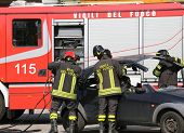 picture of firehouse  - Firefighters take off the hood of the car after a serious car accident - JPG