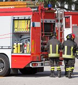picture of fire brigade  - three firefighters and fire trucks during an emergency - JPG