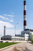 image of belching  - Work building with a large red and white chimney - JPG