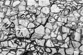 pic of graffiti  - Aged rock wall with cracks and urban spray graffiti in black and white - JPG