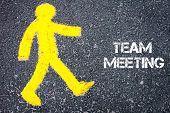 pic of pedestrians  - Yellow pedestrian figure on the road walking towards TEAM MEETING - JPG