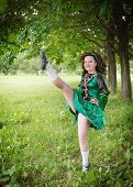 stock photo of wig  - Young beautiful girl in irish dance dress and wig dancing outdoor - JPG