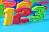 image of blue things  - Colorful plastic numbers 123 close up on a blue background - JPG