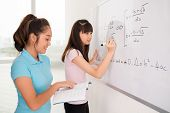 stock photo of schoolgirls  - Asian schoolgirls writing equations from the manual of algebra on the whiteboard