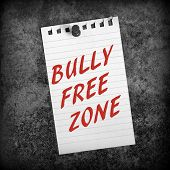 stock photo of bullying  - Black and white image of lined paper pinned to a grunge background with the phrase Bully Free Zone in red text - JPG