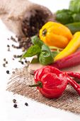 picture of yellow-pepper  - Red and yellow hot chili peppers with salt and fresh basil over white - JPG