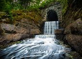 stock photo of tunnel  - Streamy waterfall at the end of a dark tunnel - JPG