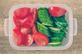 foto of lunch box  - Slice cucumber and slice tomato in plastic lunch box - JPG