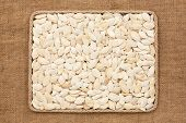 pic of sackcloth  - Frame made of rope with pumpkin seeds on sackcloth as background texture - JPG
