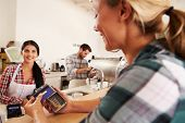 foto of internet-cafe  - Woman paying by credit card in a cafe - JPG