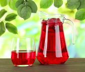 foto of pitcher  - Pitcher and glass of compote on wooden table on nature background - JPG