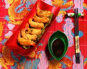 stock photo of deep  - traditional Vietnam deep fried shrimp and pork rolls in breadcrumbs served on a traditional bamboo place mat - JPG