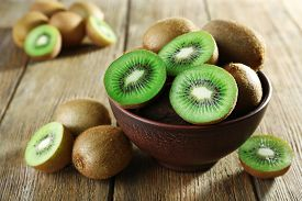 stock photo of food plant  - Juicy kiwi fruit in bowl on wooden background - JPG