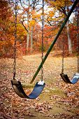 stock photo of swingset  - An old swingset in a park during the autumn season - JPG