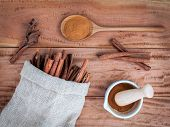 Постер, плакат: Composition Of Cinnamon Stick In Hemp Sack And Cinnamon Powder In White Mortar And Cinnamon Powder