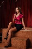 Young Woman In Red Blouse Sitting On Stage