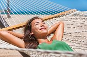 Relaxing woman sleeping on hammock in the tropical sun. Asian girl resting lying down in resort loun poster
