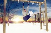 fitness, sport, exercising, training and people concept - young man doing leg pull ups on horizontal poster
