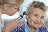 stock photo of otoscope  - Doctor performing ear exam with otoscope on a senior patient - JPG