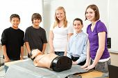 Group of teenagers with a CPR training dummy, about to learn cardiopulmonary resuscitation.