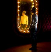stock photo of peddlers  - fashionable young man looks at himself in mirror - JPG