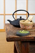 Tatami mat and green powder tea with teapot and bamboo whisk for zen ceremony