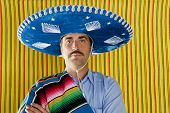 Mexican mustache man portrait with sombrero holding serape in shoulder