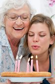 stock photo of elderly woman  - Happy smiling grandmother celebrating and giving a birthday cake to her grandson at home - JPG