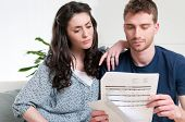 Young couple reading a financial bill or letter with worried expressions at home