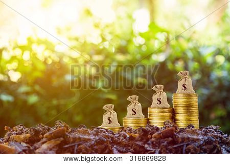 poster of Making Money And Money Investment Concept. A Money Bag On Rise Up Stack Of Coins On Good Soil And Na