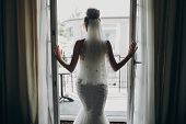 Silhouette Of Stylish Bride Opening Window Balcony In Soft Light In Hotel Room. Back Of Gorgeous Sen poster