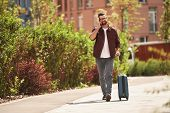 Happy To Hear You Cheerful Bearded Man In Casual Wear And Eyeglasses Pulling His Luggage And Talking poster