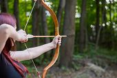Woman Archer Shooting Targets With Wooden Bow At Historical Festival. Archery And Medieval Culture C poster