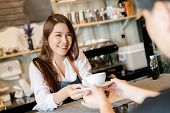 Professional Asian Woman Barista Preparing Coffee At Front Counter Serving Coffee Cup To Customer Oc poster