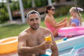 Man Drinking Cold Cocktail While Chilling With Family Near Pool poster