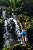 Travel Lifestyle. Young Traveler Woman Wearing Bikini At Waterfall In Tropics.  Excited  Woman Raisi poster