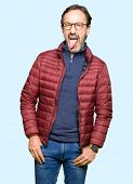 Middle age handsome man wearing glasses and winter coat sticking tongue out happy with funny express poster