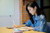 Asian Woman University Student In Casual Writing On Paper Notebook, Teenager Student Hand Writing Le poster
