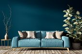 Modern Interior Of Living Room With Turquoise Sofa, Home Plant And Vase With Branch Against Blue Wal poster