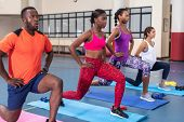 Side view of diverse fit people performing yoga together on a exercise mat in fitness center. Bright poster