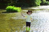 Little Child Fishing On River. Boy In Yellow Shirt With A Fishing Rod By The River. Fisherman Child  poster