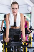 Close-up of Caucasian fit woman exercising on exercise bike in fitness center. Bright modern gym wit poster